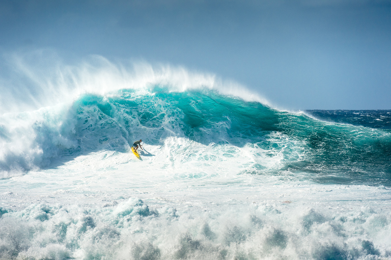 Kohl Christensen riding a mountain of water on a chaotic day at Pipeline on the north shore of Oahu, Hawaii.